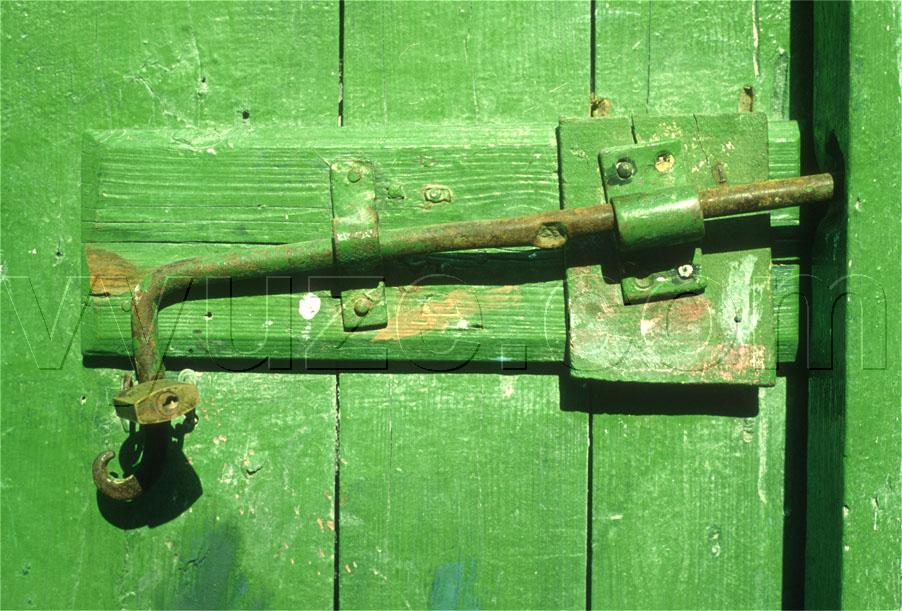 Detail of green painted wooden door and bolt fastener. / Location: Greece.