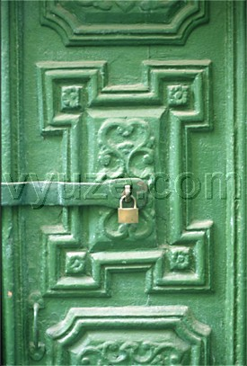 Green painted door with carving and padlock / Location: Metsovo, Epirus, Greece